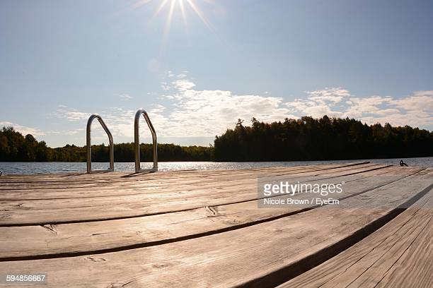 Pier And Lake Against Sky On Sunny Day