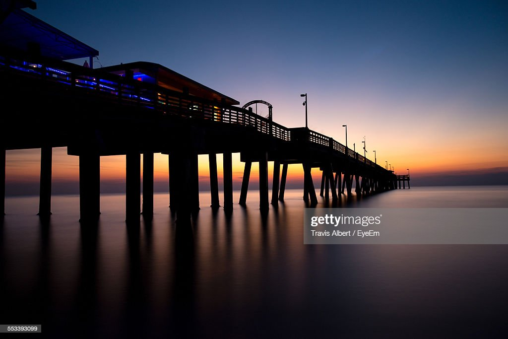 Pier In Calm Water At Dusk