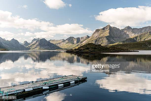 Pier in mirror water and mountain chains