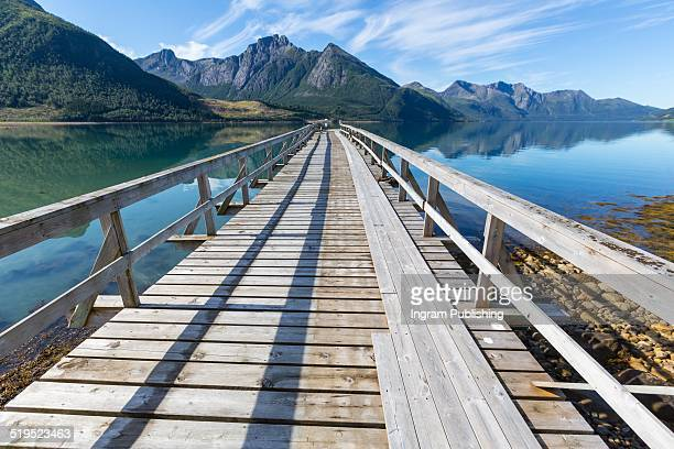 Pier leading towards mountains at Norway