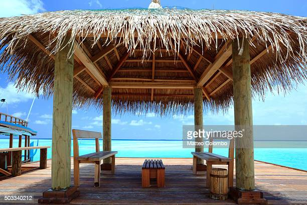 Pier on tropical island with thatched roof and chairs, Maldives