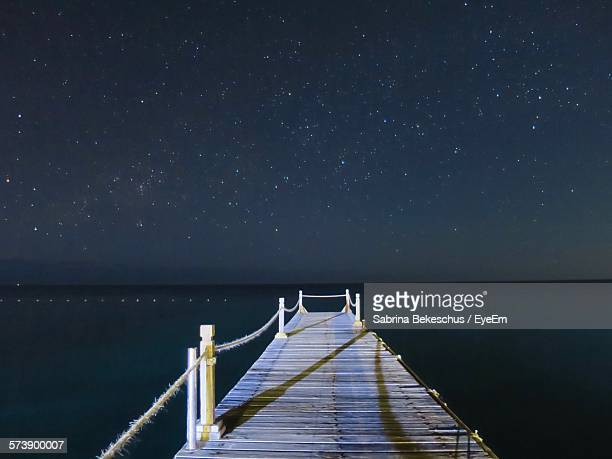 Pier Over Sea Against Star Field At Night