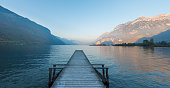 Wooden pier on the lake. Sunset in pastel colors. Mountains in the background.