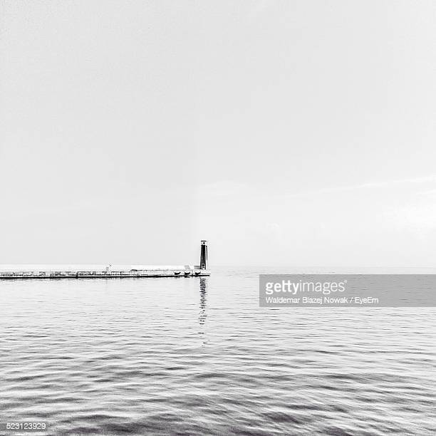 Pier With Beacon In Sea Against Clear Sky
