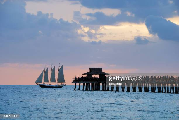 Pier with passing sailboat at dusk