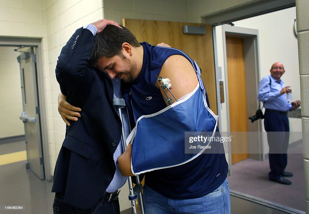 Pierce O'Farrill who was wounded during the Century 16 movie theater shooting receives a hug from Chad Weinmaster as he attends a service at The Edge church on July 29, 2012 in Aurora, Colorado. Mr. O'Farrill was wounded when James Holmes the twenty-four-year-old is suspected of killing 12 and injuring 58 others during a shooting rampage on July 20th at a screening of 'The Dark Knight Rises.'