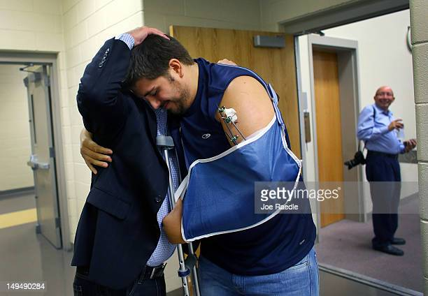 Pierce O'Farrill who was wounded during the Century 16 movie theater shooting receives a hug from Chad Weinmaster as he attends a service at The Edge...