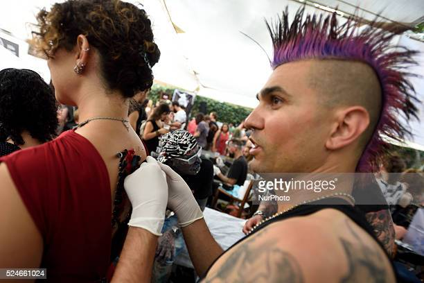 A piercing artist inserts a ribbon through piercing rings at the back of an Israeli woman during the 3rd annual tattoo convention in TelAviv on June...
