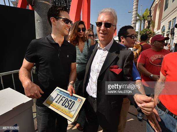 Piero Ferrari with a fan at the 'Race Through the Decades 19542014'' event to celebrate its 60th anniversary of Ferrari in the United States at...