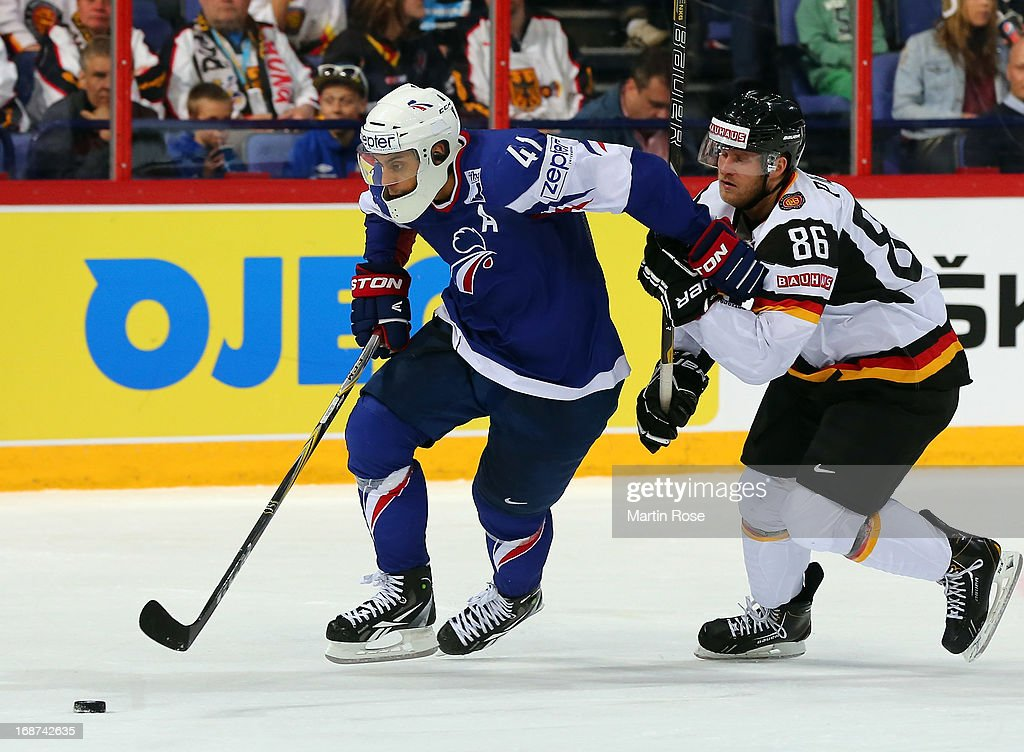 Pierre Bellemare (L) of France and Daniel Pietta (R) of Germany battle for the puck during the IIHF World Championship group H match between France and Germany at Hartwall Areena on May 14, 2013 in Helsinki, Finland.