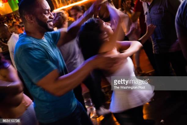 Pierre Bennett of Reston VA left spins Joanna Mendez of Jacksonville FL on the dance floor of The Lucky Bar on August 7 2017 Monday night is salsa...