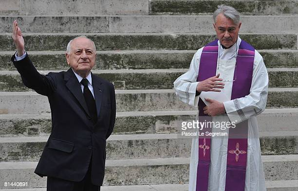 Pierre Berge waves to the crowd as Bishop Roland Letteron stands during Yves Saint Laurent's Funeral Service on June 5 2008 at Eglise SaintRoch in...