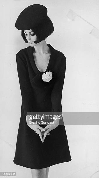 A Pierre Cardin sheath dress in navy blue crepe with plunging neckline dramatised by a single white camellia is worn with a schoolgirl style beret