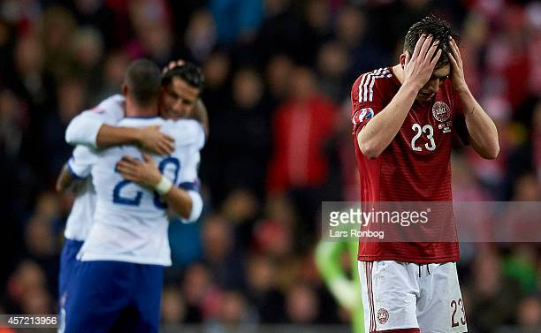 Pierre Emile Hojbjerg of Denmark looks dejected meanwhile Cristiano Ronaldo of Portugal celebrates their victory in the background after the UEFA...