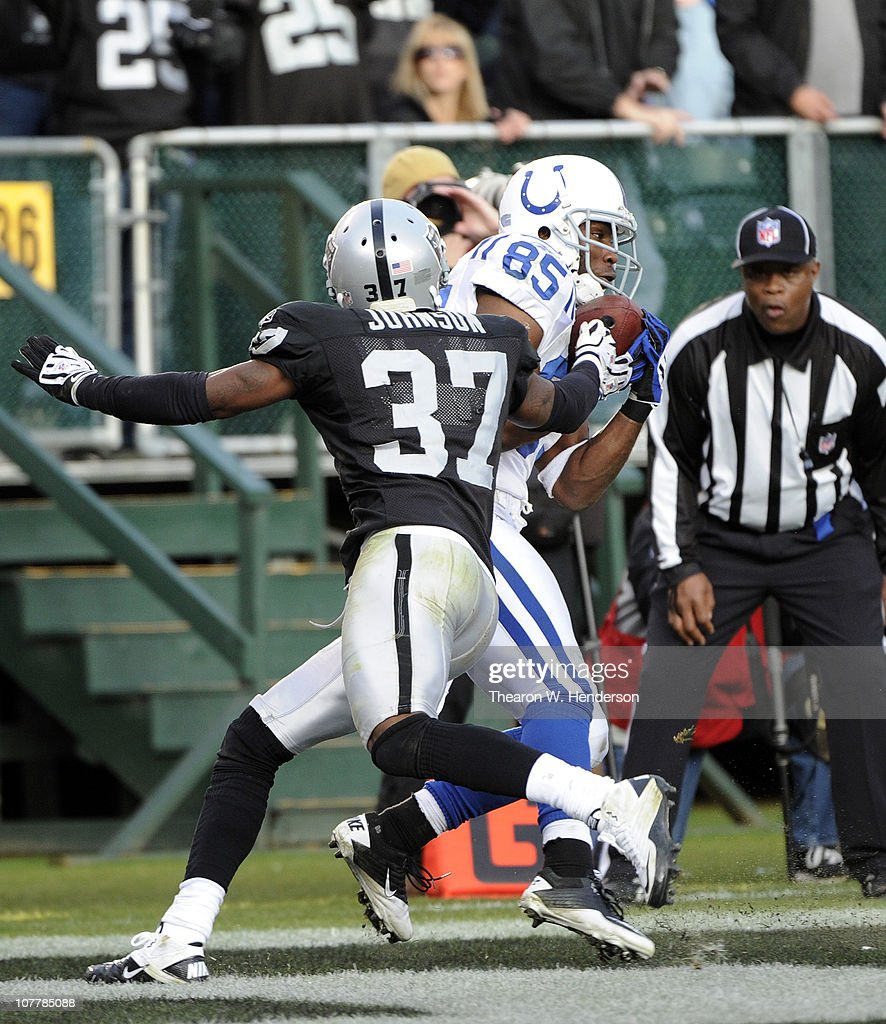 Pierre Garcon #85 of the Indianapolis Colts catches this touchdown pass over Chris Johnson #37 of the Oakland Raiders during an NFL football game at The Oakland-Alameda County Coliseum December 26, 2010 in Oakland, California. The Colts won the game 31-26.