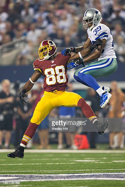 Pierre Garcon of the Washington Redskins and Brandon Carr of the Dallas Cowboys jump for a pass at ATT Stadium on October 13 2013 in Arlington Texas...