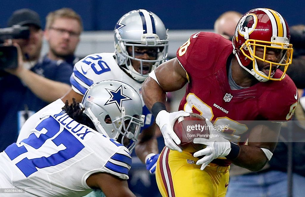 Pierre Garcon of the Washington Redskins catches a touchdown pass against JJ Wilcox and Deji Olatoye of the Dallas Cowboys during the first half at...