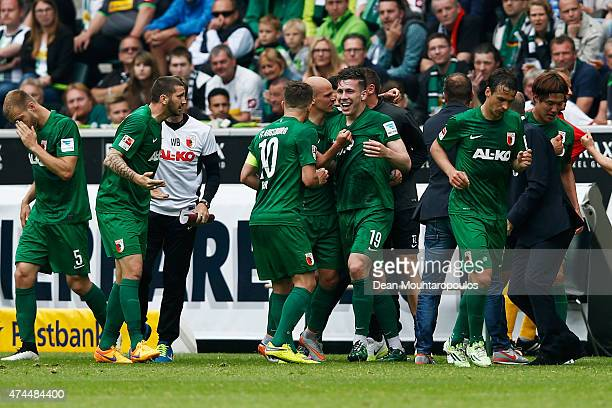 Pierre Hojbjerg of FC Augsburg celebrates scoring his teams first goal of the game with his bench during the Bundesliga match between Borussia...