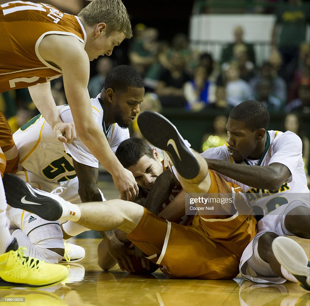 Pierre Jackson #55 and A.J. Walton #22 of the Baylor University Bears fight for a lose ball with Ioannis Papapetrou #33 of the University of Texas Longhorns on January 5, 2013 at the Ferrell Center in Waco, Texas.