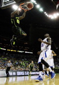 Pierre Jackson of the Baylor Bears dunks over Tyshawn Taylor of the Kansas Jayhawks in the first half during the semifinals of the 2012 Big 12 Men's...