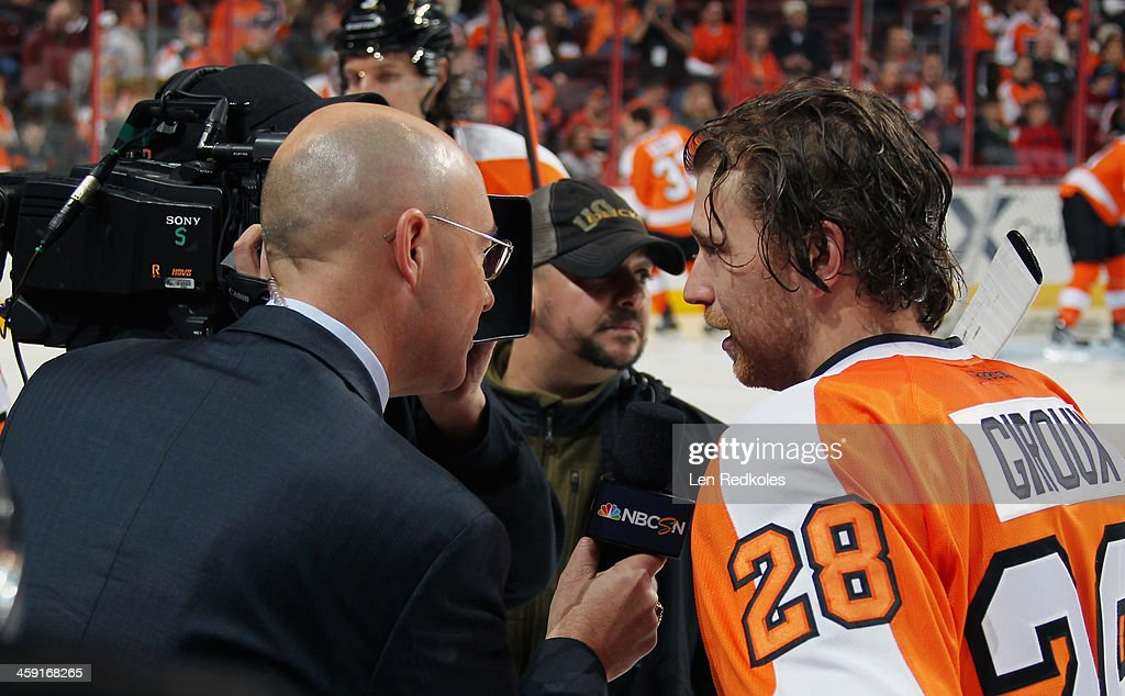 Pierre McGuire of NBC Sports Network speaks with Claude Giroux #28 of the Philadelphia Flyers during warmups prior to his game against the Minnesota Wild on December 23, 2013 at the Wells Fargo Center in Philadelphia, Pennsylvania.