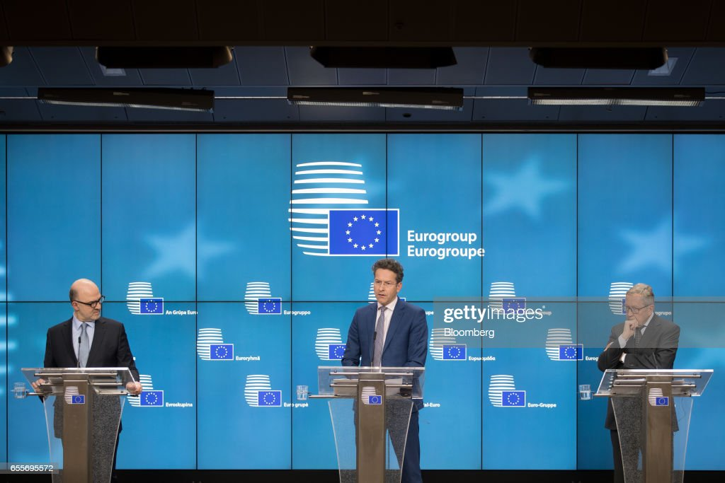 Pierre Moscovici, economic commissioner for the European Union (EU), from left, Jeroen Dijsselbloem, Dutch finance minister and head of the group of euro-area finance ministers, and Klaus Regling, managing director of the European Stability Mechanism, participate in a news conference following a Eurogroup meeting of finance ministers in Brussels, Belgium, on Monday, March 20, 2017. Wolfgang Schaeuble, Germany's finance minister, said to reporters ahead of the meeting of euro-area finance ministers We'll get a report on Greece, but the mission isn't completed. Photographer: Jasper Juinen/Bloomberg via Getty Images