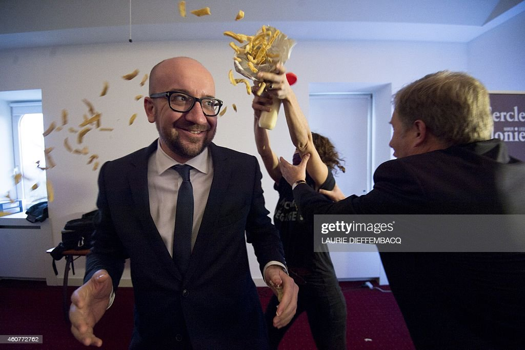 Pierre Rion (R) tries to intervene as activists throw fries and mayonnaise on Belgian Prime Minister <a gi-track='captionPersonalityLinkClicked' href=/galleries/search?phrase=Charles+Michel+-+Politician&family=editorial&specificpeople=13722663 ng-click='$event.stopPropagation()'>Charles Michel</a>, a protest action of feminist activists LilithS (formerly the Belgian branch of Femen), at a conference of Prime Minister Michel at the Cercle de Wallonie, in Namur, on December 22, 2014. AFP PHOTO / LAURIE DIEFFEMBACQ
