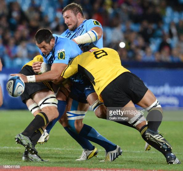 Pierre Spies of Bulls is tackled by Victor Vito of the Hurricanes during the Super Rugby match between Vodacom Bulls and Hurricanes at Loftus...