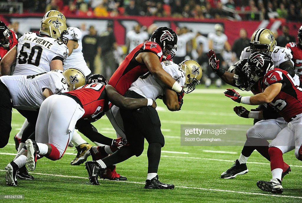 <a gi-track='captionPersonalityLinkClicked' href=/galleries/search?phrase=Pierre+Thomas&family=editorial&specificpeople=937507 ng-click='$event.stopPropagation()'>Pierre Thomas</a> #23 of the New Orleans Saints carries the ball against <a gi-track='captionPersonalityLinkClicked' href=/galleries/search?phrase=Stansly+Maponga&family=editorial&specificpeople=7363524 ng-click='$event.stopPropagation()'>Stansly Maponga</a> #90, Corey Peters #91, and <a gi-track='captionPersonalityLinkClicked' href=/galleries/search?phrase=Sean+Weatherspoon&family=editorial&specificpeople=4532907 ng-click='$event.stopPropagation()'>Sean Weatherspoon</a> #56 of the Atlanta Falcons at the Georgia Dome on November 21, 2013 in Atlanta, Georgia.