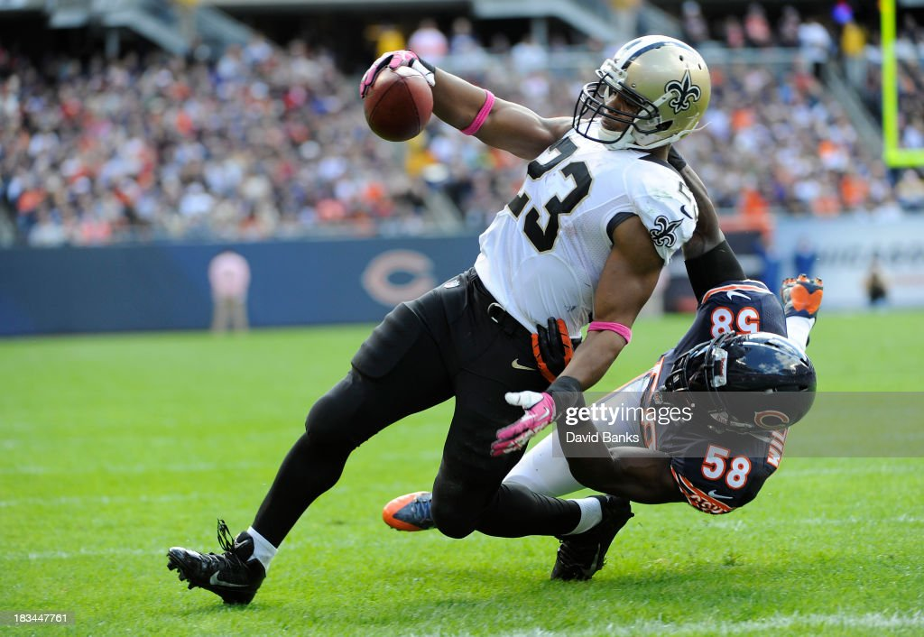 <a gi-track='captionPersonalityLinkClicked' href=/galleries/search?phrase=Pierre+Thomas&family=editorial&specificpeople=937507 ng-click='$event.stopPropagation()'>Pierre Thomas</a> #23 of the New Orleans Saints catches a touchdown pass as he's defended by <a gi-track='captionPersonalityLinkClicked' href=/galleries/search?phrase=D.J.+Williams+-+American+Football+Linebacker&family=editorial&specificpeople=224565 ng-click='$event.stopPropagation()'>D.J. Williams</a> #58 of the Chicago Bears during the second quarter on October 6, 2013 at Soldier Field in Chicago, Illinois.