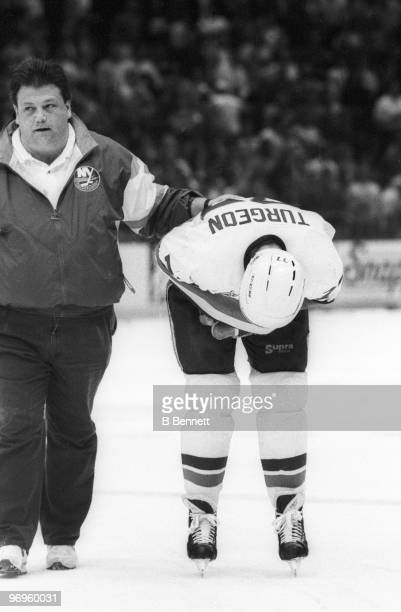 Pierre Turgeon of the New York Islanders is helped to the bench after a vicious hit by Dale Hunter of the Washington Capitals after Turgeon scored...