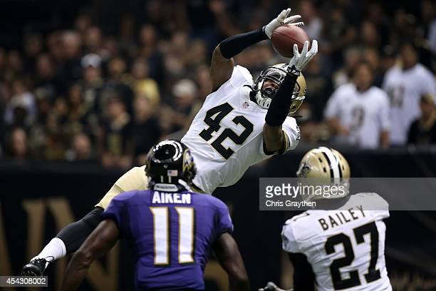 Pierre Warren of the New Orleans Saints intercepts a pass over Kamar Aiken of the Baltimore Ravens and Champ Bailey of the New Orleans Saints during...