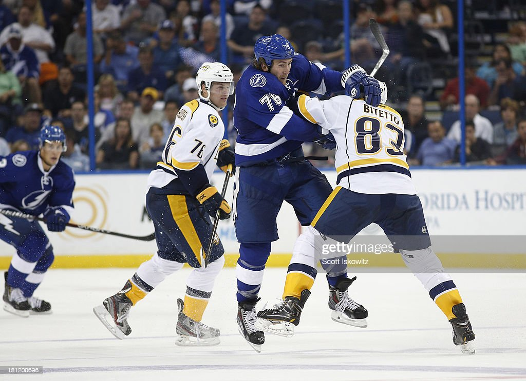 Pierre-Cedric Labrie #76 of the Tampa Bay Lightning collides with Anthony Bitetto #83 of the Nashville Predators during the second period in a preseason game at Tampa Bay Times Forum on September 19, 2013 in Tampa, Florida.