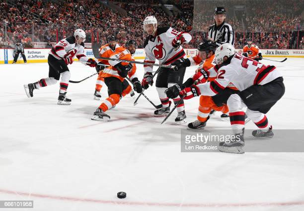 PierreEdouard Bellemare and Chris VandeVelde of the Philadelphia Flyers battle for the loose puck against Travis Zajac and Michael Kapla of the New...
