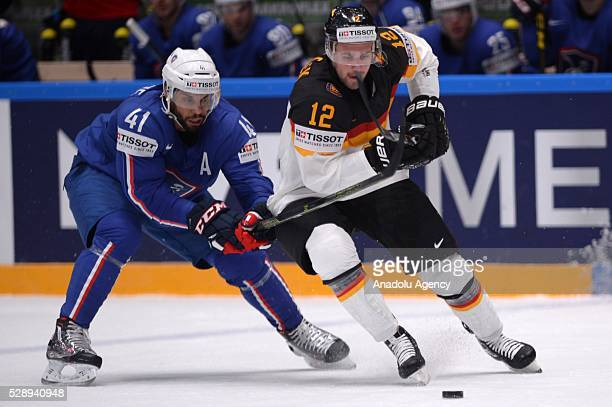 PierreEdouard Bellemare of France vies with Brooks Macek of Germany during the IIHF Ice Hockey World Championship Group B preliminary round game...