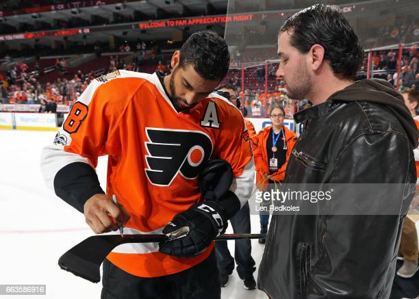 PierreEdouard Bellemare of the Philadelphia Flyers autographs his stick for a fan during a postgame Fan Appreciation Night ceremony after defeating...
