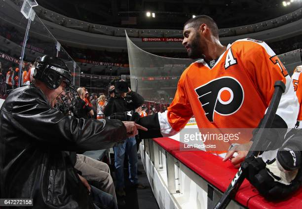 PierreEdouard Bellemare of the Philadelphia Flyers chats with fans on the bench during warmups prior to his game against the Florida Panthers on...