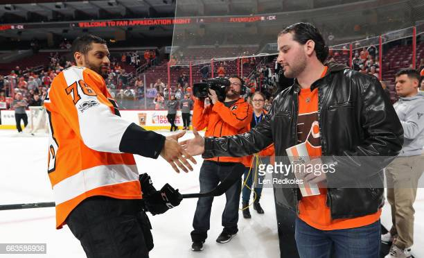 PierreEdouard Bellemare of the Philadelphia Flyers shakes hands with a fan during a postgame Fan Appreciation Night ceremony after defeating the...