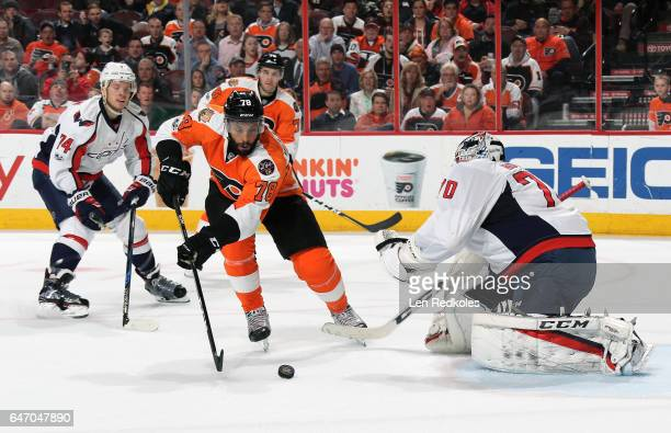 PierreEdouard Bellemare of the Philadelphia Flyers skates the puck in for a shot on goal against John Carlson and Braden Holtby of the Washington...