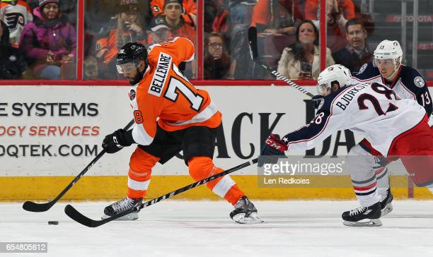 PierreEdouard Bellemare of the Philadelphia Flyers skates the puck against Oliver Bjorkstrand and Cam Atkinson of the Columbus Blue Jackets on March...