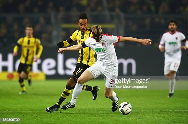PierreEmerick Aubameyang of Borussia Dortmund challenges Martin Hinteregger of FC Augsburg during the Bundesliga match between Borussia Dortmund and...