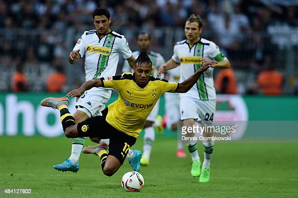PierreEmerick Aubameyang of Borussia Dortmund is challenged by Lars Stindl of Borussia Moenchengladbach during the Bundesliga match between Borussia...