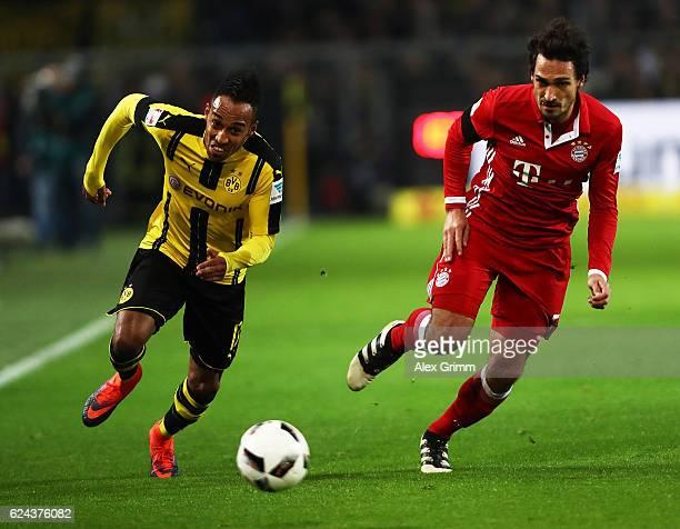 PierreEmerick Aubameyang of Borussia Dortmund is challenged by Matts Hummels of Bayern Munich during the Bundesliga match between Borussia Dortmund...