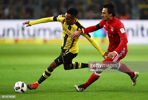 PierreEmerick Aubameyang of Borussia Dortmund is challenged by Matts Hummels of Bayern Munich during the Bundesliga match between Borussia Dortmund...