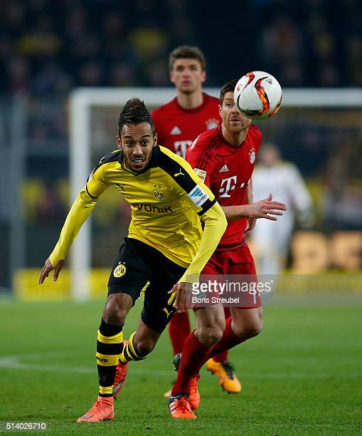 PierreEmerick Aubameyang of Borussia Dortmund is challenged by Xabi Alonso of Bayern Munich during the Bundesliga match between Borussia Dortmund and...