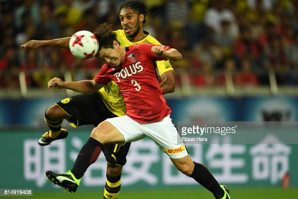 PierreEmerick Aubameyang of Burussia Dortmund and Tomoya Ugajin of Urawa Red Diamonds compete for the ball during the preseason friendly match...