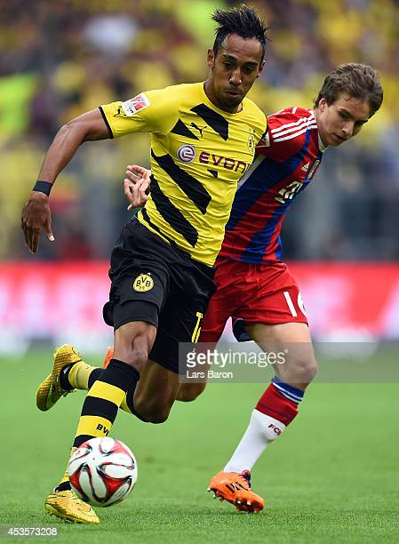 PierreEmerick Aubameyang of Dortmund is challenged by Gianluca Guadino of Munich during the DFL Supercup between Borrussia Dortmund and FC Bayern...