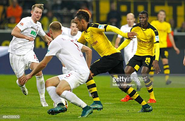 PierreEmerick Aubameyang of Dortmund kicks the 51 against JanIngwer CallsenBracker of Augsburg and Ragnar Klavan of Augsburg during the Bundesliga...