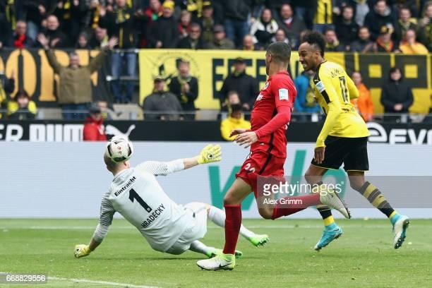 PierreEmerick Aubameyang of Dortmund scores his team's third goal past goalkeeper Lukas Hradecky of Frankfurt during the Bundesliga match between...