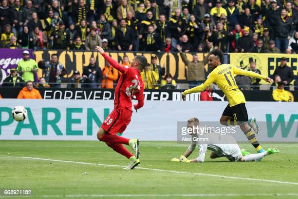 PierreEmerick Aubameyang of Dortmund scores his team's third goal past goalkeeper Lukas Hradecky and Omar Mascarell of Frankfurt during the...